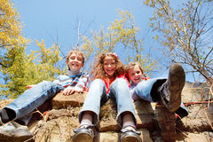 Laughing kids. Three laughing kids sitting on the stone walls Royalty Free Stock Photography