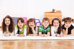 Laughing kids. Group of laughing kids lying on floor Royalty Free Stock Photos