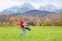 Laughing kids in field between snow mountains Stock Photos