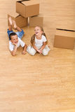 Laughing kids on the floor. Kids on the floor in their new home with cardboard boxes - large copy space stock images