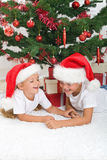 Laughing kids in front of the christmas tree Royalty Free Stock Images