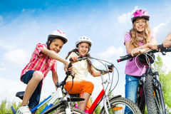Laughing kids in helmets hold bike handle-bars. Three laughing kids in helmets hold bike handle-bars and are ready to ride a bike Royalty Free Stock Photos