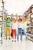 Laughing kids jump with hands up in the library Stock Photo