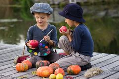 Laughing kids paint small Halloween pumpkins. On the river bank Stock Images
