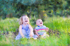 Laughing kids playing in a forest. Happy little children, adorable toddler girl in a blue dress and a cute baby boy, brother and sister, playing together with royalty free stock image
