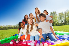 Laughing kids sitting in the center of parachute. Group of laughing kids, 10 years old boys and girls, sitting in the center of rainbow parachute full of Stock Image