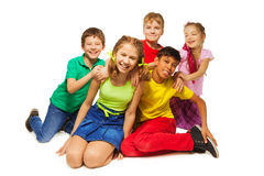 Laughing kids sitting on the floor together. On the white background stock images