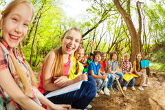 Laughing kids sitting on a log in the summer camp Royalty Free Stock Image