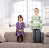 Laughing kids standing on couch Royalty Free Stock Images