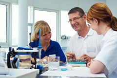 Laughing in a lab. Three dental technicians working in a dental laboratory Royalty Free Stock Photography