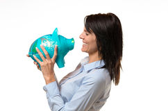 Laughing lady holding a piggy bank in her hands Royalty Free Stock Images