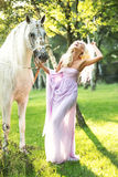 Laughing lady walking with horse royalty free stock photo