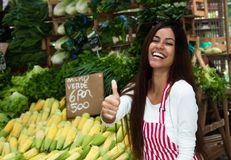 Laughing latin american saleswoman at farmers market with corn a. Laughing latin american saleswoman outdoors at farmers market with corn and vegetables royalty free stock image