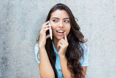 Laughing latin american woman at cellphone Royalty Free Stock Image
