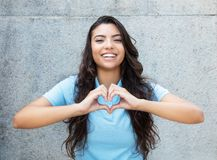 Laughing latin american woman in love showing heart with hands Stock Photo