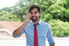 Laughing latin businessman with beard at mobile phone. Outdoors Royalty Free Stock Images