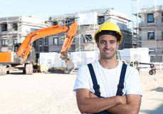 Laughing latin construction worker with crossed arms and red excavator Royalty Free Stock Photo