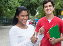 Laughing latin female student showing thumb with caucasian friend Royalty Free Stock Images