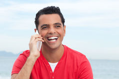 Laughing latin guy at beach happy at phone. Ocean and sky in the background Royalty Free Stock Photography
