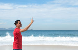 Laughing latin guy at beach pointing at sky Royalty Free Stock Image