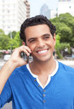 Laughing latin guy with cell phone in the city Royalty Free Stock Photos