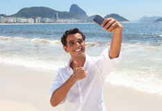 Laughing latin guy making selfie at Copacabana beach Royalty Free Stock Photo