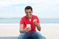 Laughing latin guy in red shirt writing message at phone Stock Photography