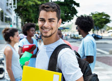 Laughing latin male student with group of friends Stock Photo