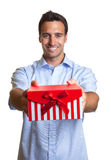 Laughing latin man hands over the christmas present Royalty Free Stock Photo