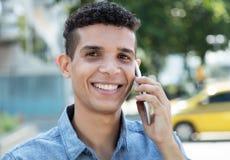 Laughing latin man at phone in city. Laughing latin man at phone outdoor in the city Stock Images