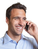 Laughing latin man talking to his girlfriend. Handsome latin man with stubble talking to his girlfriend on the phone stock photography