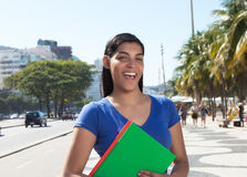 Laughing latin student with long dark hair in the city Stock Photo