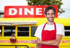 Laughing latin waiter with food truck. Laughing latin waiter in front of his food truck Stock Photo