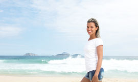 Laughing latin woman with blonde hair walking at beach. With with ocean waves and blue sky in the background Stock Photo