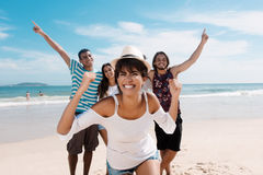 Laughing latin woman with cheering young adults at beach Royalty Free Stock Photography