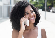 Laughing latin woman with curly black hair at phone. Outdoor in the summer Royalty Free Stock Image