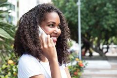 Laughing latin woman with curly hair at phone in a park Royalty Free Stock Photo