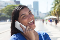 Laughing latin woman with long dark hair at phone in city Royalty Free Stock Photo