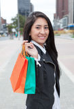 Laughing latin woman with two shopping bags Stock Images