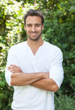Laughing latinman with crossed arms in a park Stock Photo