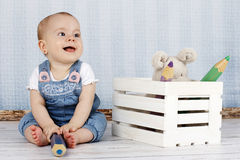 Laughing little baby girl with big pencil and plush toys Royalty Free Stock Image