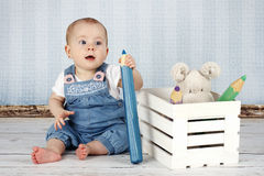 Laughing little baby girl with big pencil and plush toys Royalty Free Stock Images