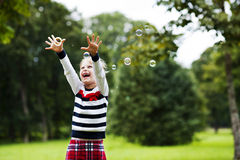 Laughing little blonde girl playing with soap bubbles in park. Emotional laughing  little blonde girl playing/catching soap bubbles in the green summer park Stock Photo