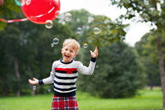 Laughing little blonde girl playing with soap bubbles in park. Emotional laughing little blonde girl playing/catching soap bubbles in the green summer park Stock Photography