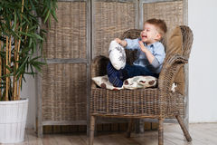 Laughing little boy. Sits in a armchair Royalty Free Stock Photo