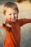Laughing little boy. In orange evening sunlight; blurred background Royalty Free Stock Photography