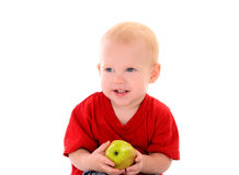Laughing little boy with apple Stock Images