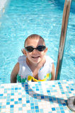 Laughing little boy climbing out of a pool Stock Images