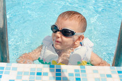 Laughing little boy climbing out of a pool Stock Photo