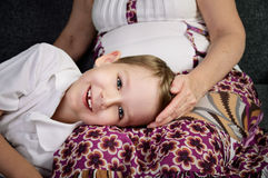 Laughing little boy looking at camera and his loving grandmother Stock Image